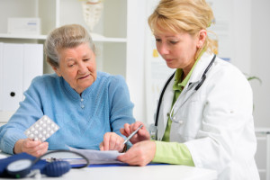 Doctor showing a medication to an older patient