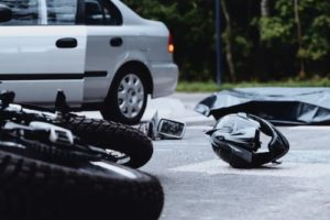 motorcycle and motorcycle helmet on the ground after an accident with a car