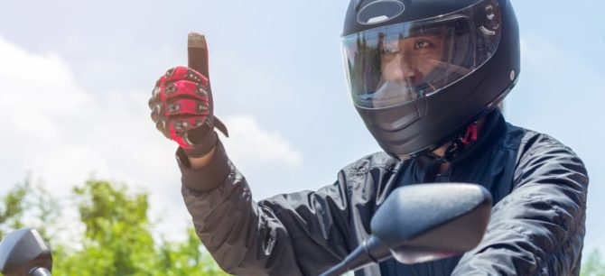 man wearing helmet with thumb point up